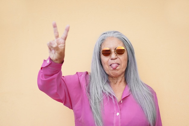Cool granny wearing hippie eye glasses and doing peace gesture - old woman with tongue out