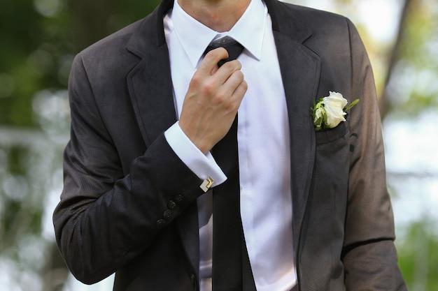 クールな新郎は完全な成長で彼のネクタイをまっすぐにします。