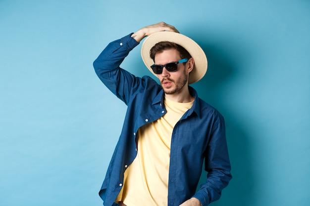 休暇で楽しんで、麦わら帽子とサングラスを身に着けて、生意気な脇を見て、青い背景の上に立っているクールな男。
