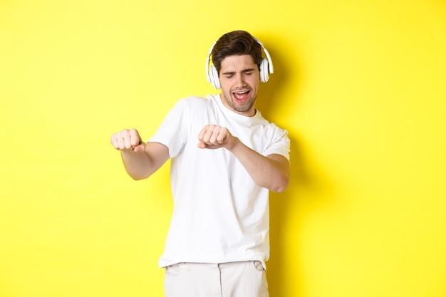 Cool guy ascoltando musica in cuffia e balli, in piedi in abiti bianchi su sfondo giallo studio.