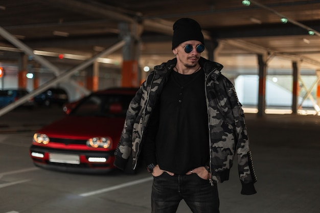 Cool guy in a military jacket with glasses and hat walking outdoors in a parking lot