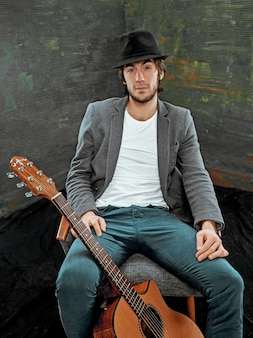Cool guy sitting with guitar on gray