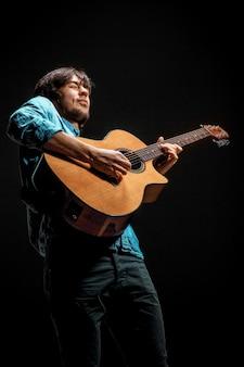 暗い空間にギターで立っているクールな男