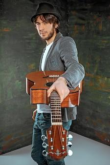 회색 벽에 기타와 함께 서있는 멋진 남자