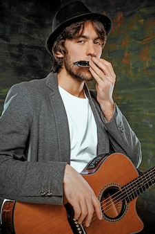 灰色のスタジオの背景にギターとハーモニカーを演奏する帽子のクールな男