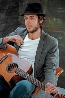 회색 스튜디오 배경에 기타와 함께 앉아 모자와 멋진 남자