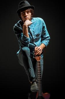 Ragazzo freddo con il cappello in piedi con la chitarra su sfondo scuro studio