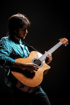 어두운 스튜디오 배경에 기타와 함께 서있는 모자와 함께 멋진 남자
