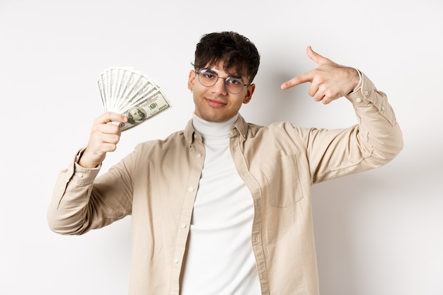Cool handsome guy show-off his income, pointing at dollar bills and smiling boastful, making money, standing on white wall.