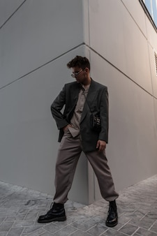 Cool handsome hipster man with glasses in fashionable clothes with jacket, shirt, trousers and shoes near gray background in city