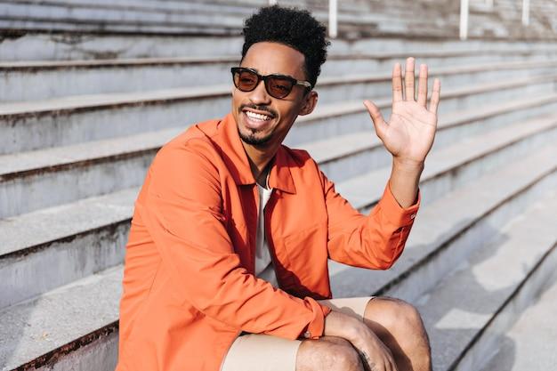 サングラスとオレンジ色のジャケットの笑顔でクールな幸せな黒髪の浅黒い肌の男は、挨拶で手を振って、階段に座っています