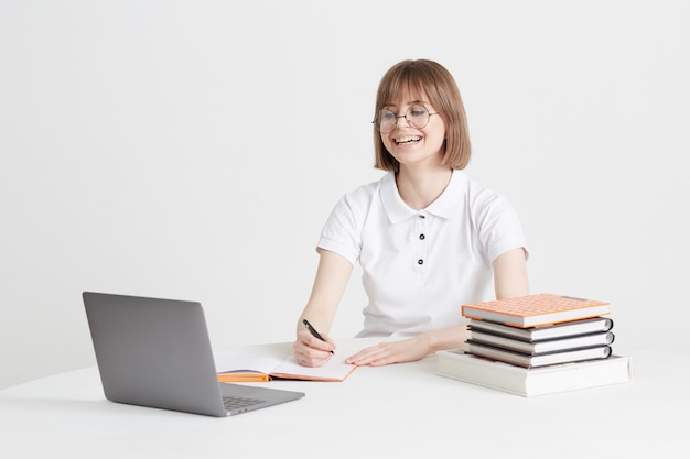 멋진 행복 한 여자는 집에 앉아 온라인 교육을 통해 간다. 노트북에 원격 학교 교육입니다. 홈 레슨을 유지하십시오.