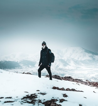 Cool hiker in a mask and dark clothes standing alone on a snowy steep hill in the mountains