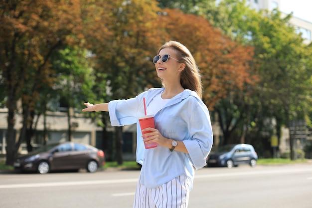 멋진 힙스터 소녀가 야외에서 즐거운 시간을 보내고 있습니다. 도시 배경에서 택시를 호출합니다.
