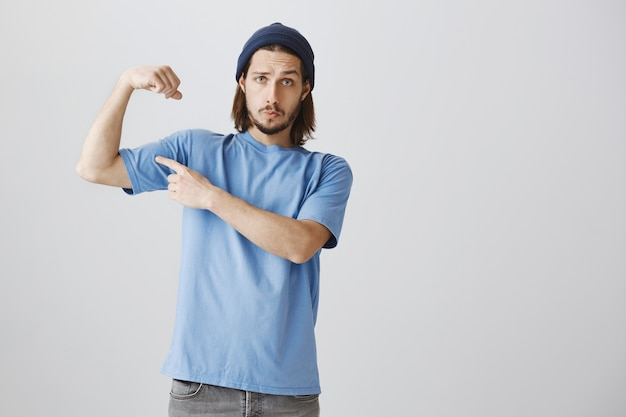 Cool hipster guy in blue t-shirt and beanie flex biceps, bragging with strong muscles