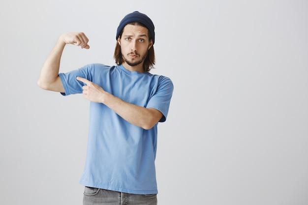 Крутой хипстерский парень в синей футболке и шапочке сгибает бицепсы, хвастаясь сильными мускулами