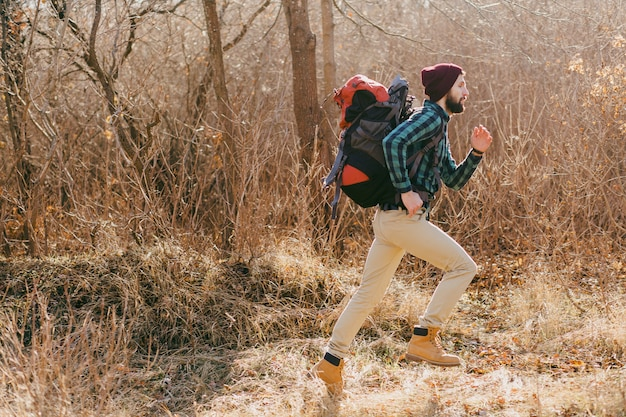 Cool hipster man traveling with backpack in autumn forest wearing checkered shirt and hat, active tourist running, exploring nature in cold season