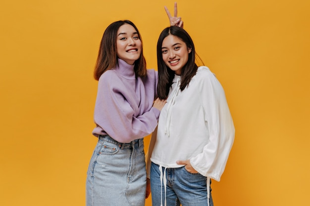 Cool joyful girl in purple sweater gives bunny ears to her smiling friend