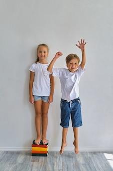 멋진 아이들, 어린 소년 소녀가 자신의 키를 측정하고 비교하고 흰 벽 근처에서 즐거운 시간을 보내세요