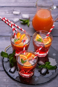 Cool lemonade with oranges, soda, raspberry syrup, mint leaves on dark wooden table
