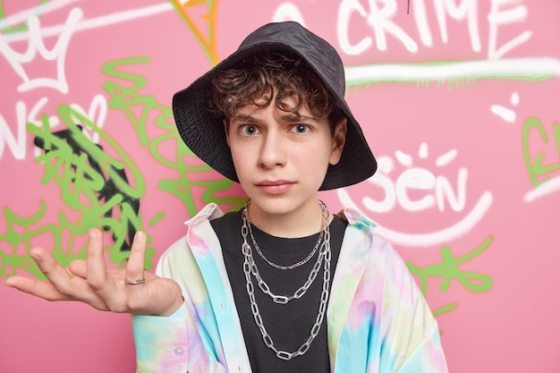 Cool looking indignant youngster shrugs shoulders and looks clueless at camera dressed in fashionable clothes poses against graffiti wall poses at urban place