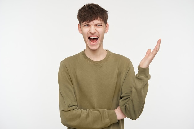 Cool looking male, emotional guy with brunette hair, piercing and bristle. wearing khaki color sweater. angry yelling with hand lifted. isolated over white wall