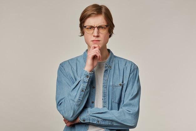 Ragazzo dall'aspetto fresco, uomo concentrato con i capelli biondi. indossare occhiali e camicia di jeans. si tocca il mento e si acciglia. concetto di emozione. guardando minuziosamente isolato sopra il muro grigio
