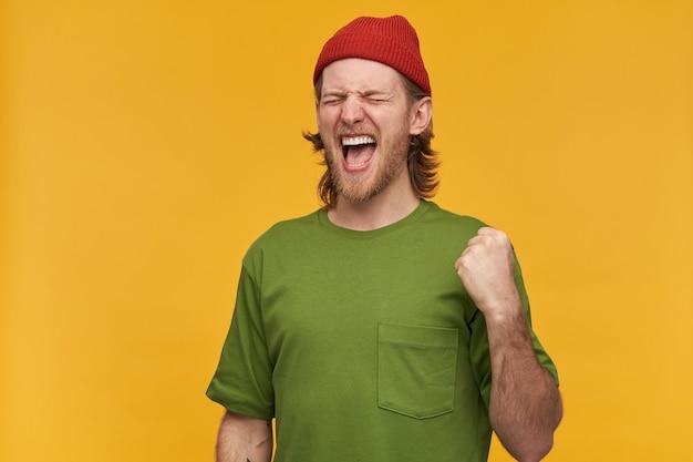 Крутой мужчина, красивый бородатый парень со светлыми волосами. в зеленой футболке и красной шапке. сжимайте кулак от волнения, праздника. стенд с закрытыми глазами, изолированные на желтой стене
