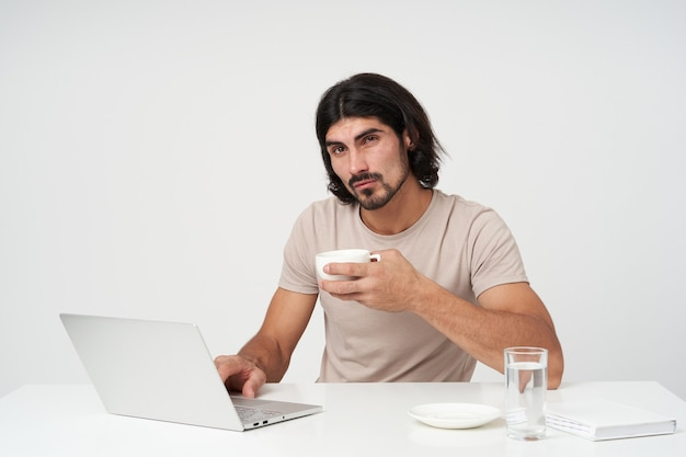 Cool looking male, handsome businessman with black hair and beard. office concept. sitting in work place and having coffee break. holds a cup.  isolated over white wall
