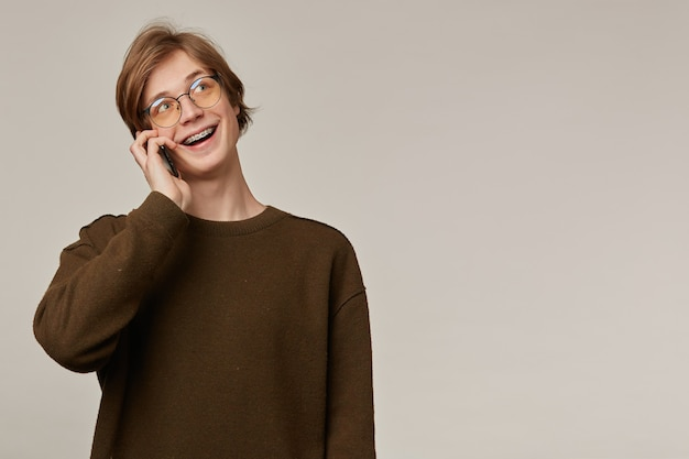 かっこいい男性、ブロンドの髪のハンサムな男。茶色のセーターと眼鏡をかけています。中かっこがあります。