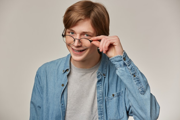 금발 머리를 가진 멋진 찾고 남성, 잘 생긴 남자. 데님 셔츠와 안경 착용. 중괄호가 있습니다. 그의 안경을 만지고 웃고 있습니다. 감정 개념.