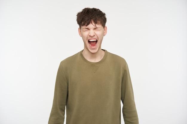 Крутой на вид мужчина, симпатичный парень с волосами брюнетки, пирсингом и щетиной. в свитере цвета хаки. сильно кричать с закрытыми глазами, кричать от гнева. стенд, изолированные на белой стене