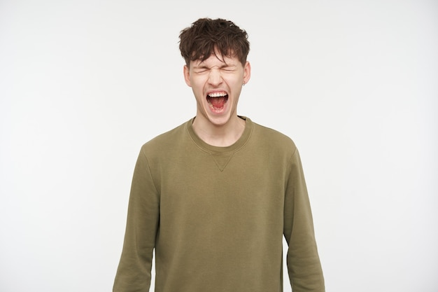 Cool looking male, handsome guy with brunette hair, piercing and bristle. wearing khaki color sweater. yelling hard with closed eyes, shout in anger. stand isolated over white wall