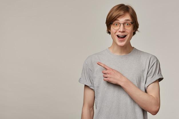 かっこいい男性、ブロンドの髪のポジティブな男。灰色のtシャツと眼鏡をかけています。中かっこがあります。灰色の壁の上に隔離されたコピースペースを左に指で指す