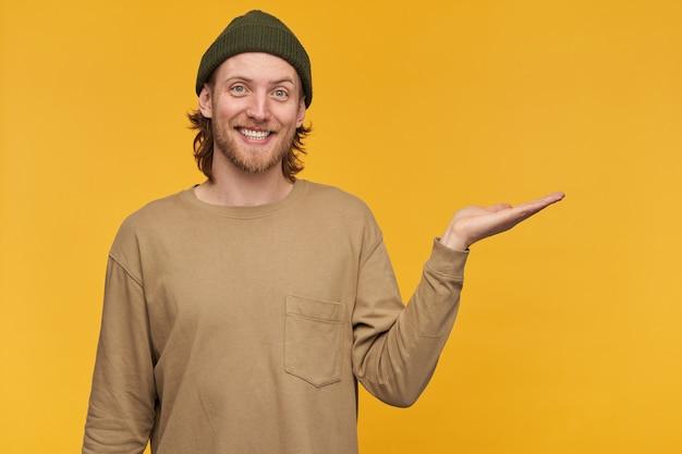 Крутой мужчина, красивый бородатый парень со светлой прической. в зеленой шапке и бежевом свитере. и указывая ладонью вправо на пространство для копирования, изолированное над желтой стеной