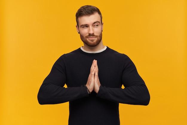 Крутой мужчина, красивый парень с волосами брюнетки и бородой. имеет пирсинг. в черном свитере. держит ладони в жесте намасте. наблюдая за кокеткой справа в пространстве для копирования, изолированном над желтой стеной