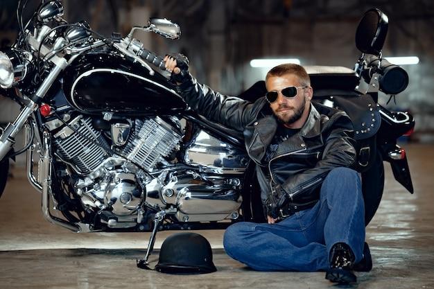 Крутой байкер в темных очках сидит возле своего мотоцикла