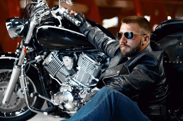 Крутой байкер в солнцезащитных очках сидит возле своего мотоцикла