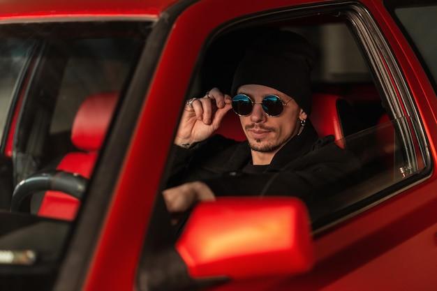 세련된 옷을 입은 멋진 남자는 오래된 차를 타고 운전하고 선글라스를 조정합니다