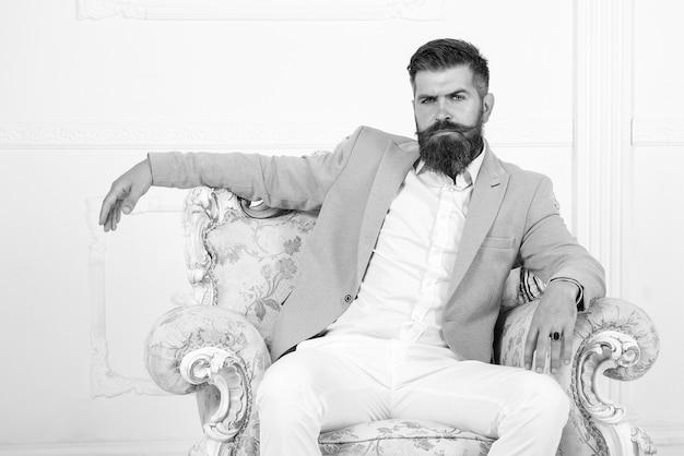 공식적인 옷을 입은 멋진 남자, 흰색 배경, 주식, 주식, 돈 위에 의자에 앉아 있습니다. 그의 피에 왕족. 고급스러운 인테리어의 자에 앉아 가벼운 정장을 입은 사려깊은 섹시한 잘생긴 남자. 손가락 반지