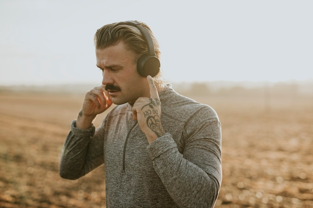 Крутой человек слушает музыку в беспроводных наушниках