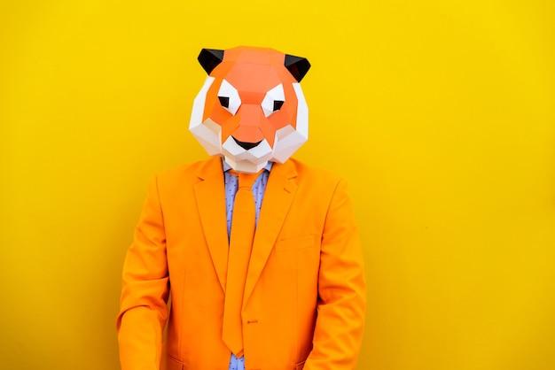 세련된 색깔의 옷을 입고 3d 종이 접기 마스크를 쓰고 멋진 남자-광고에 대한 창의적인 개념, 화려한 배경에 재미있는 일을하는 동물 머리 마스크