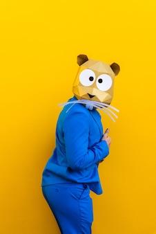 화려한 배경에 재미있는 일을하는 동물 머리 마스크 광고에 대한 세련된 색깔의 옷 창조적 인 개념으로 3d 종이 접기 마스크를 쓰고 멋진 남자