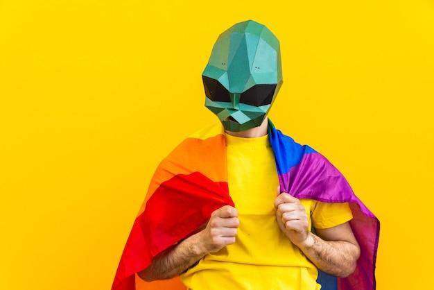 スタイリッシュな色の服と3d折り紙マスクを身に着けているクールな男カラフルな背景で面白いことをしている動物の頭のマスクを宣伝するための創造的なコンセプト