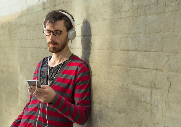 A cool man with a beard hipster listens to music, uses a smartphone.