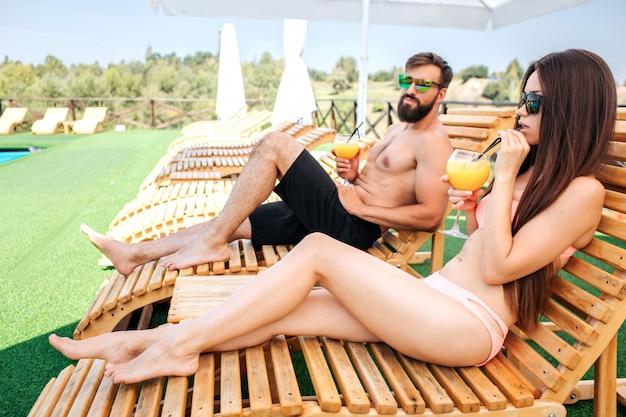 Крутая картина молодой мужчина и женщина, сидя на шезлонгах. девушка пьет коктейль и смотрит прямо вперед. парень носит солнцезащитные очки и смотрит на нее. они немного отдыхают.