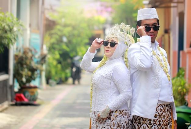 자바 인 무슬림 관습을 가진 아시아 신부 커플을위한 멋진 포즈