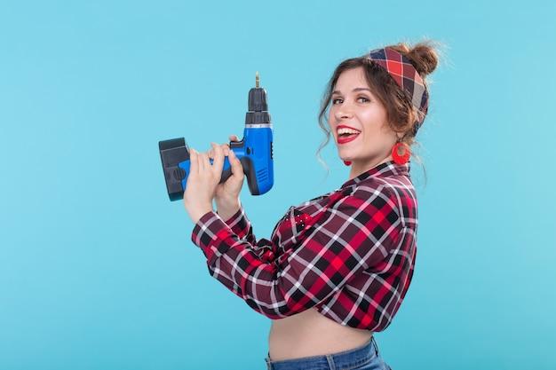 파란색 표면에 포즈 드라이버를 들고 격자 무늬 셔츠에 멋진 긍정적 인 젊은 여자
