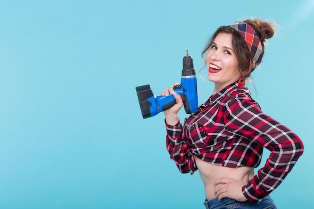 파란색 벽에 포즈 드라이버를 들고 격자 무늬 셔츠에 멋진 긍정적 인 젊은 여자. 수리 및 건설의 개념. 광고 공간