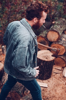 Классный рыжий парень с серьгой, курит сигарету и готовится рубить дрова. он снимает джинсовую куртку. брутальное мужское впечатление